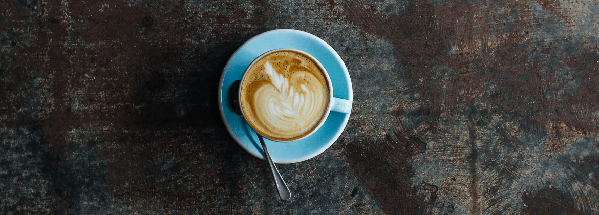 latte art shown in a cup of coffee sitting on a brown/brassy table. the cup is blue and has a matching saucer. there is a teaspoon sitting on the left hand side of the cup