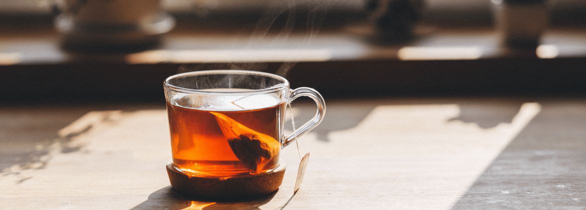 a cup of tea brewing with tea bag still inside. the cup is made of glass so you can see the teabag through it. there is sun coming in from a window behind the cup